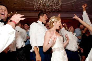 immodestly dressed men and women dancing to modern music at a wedding reception