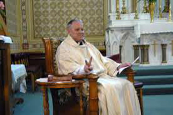A priest sitting in a chair and 'presiding' over the mass